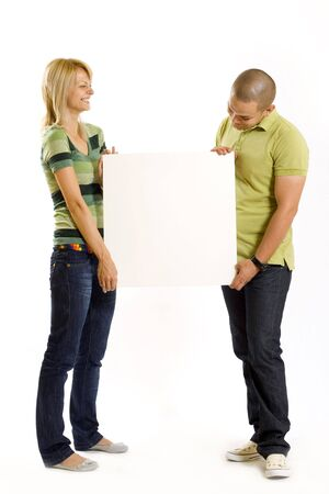 young couple presenting a blank board over white background photo