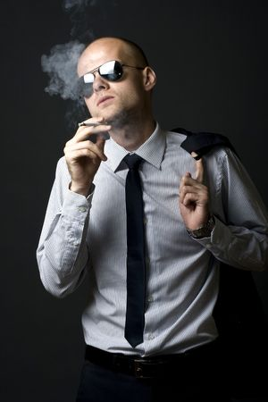 Young businessman smoking with coat on shoulder photo