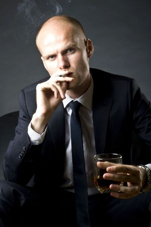 blue eyed businessman siting on a sofa and smoking a cigarette and drinking whiskey photo