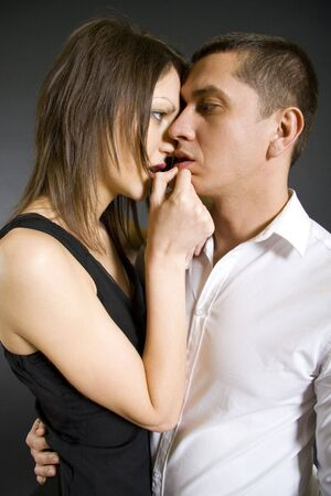 Fashion Couple- woman taking on her partner lips photo