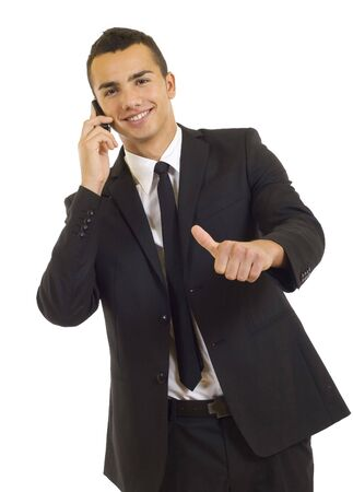 Happy businessman showing thumb up while talking on the phone  photo
