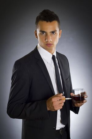 businessman smoking a cigarette and drinking whiskey over dark background photo