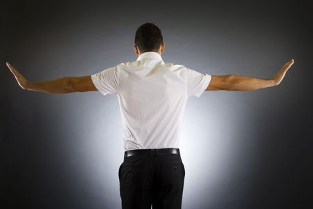 facing away: Stock photo of the back side of a well dressed businessman holding his arms up