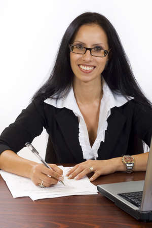 Business woman at her desk working signing papers photo