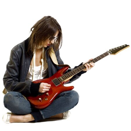 passionate rock girl playing an electric guitar sitting down photo