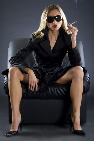A beautiful spy lady sitting on a sofa, smoking a cigarrette photo