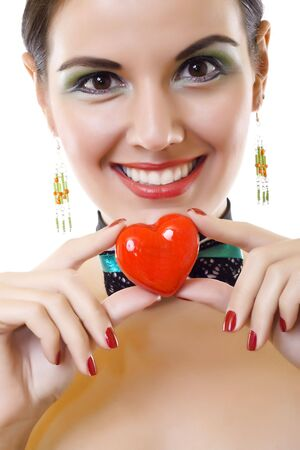 young pretty girl holding heart and smiling over white photo