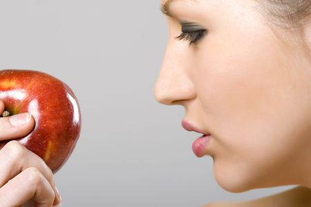 furtive: closeup picture of a woman looking at an apple
