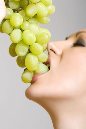 closeup picture of a woman biting a grape photo
