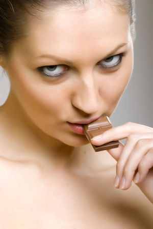 Sexy girl eating chocolate, closeup picture over grey background Stock Photo - 6393939