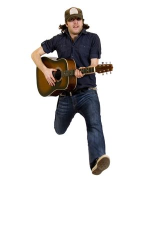 passionate guitarist playing an acoustic guitar jumps over white
