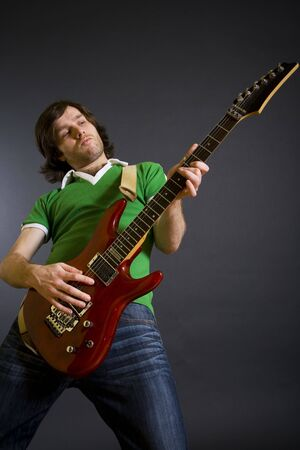 harmonist: Electric guitar player on a dark background playing the rock music