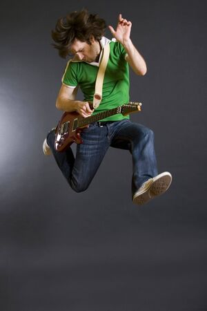 passionate guitarist jumps in the air over dark background