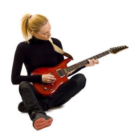 bass guitar women: passionate rock girl playing an electric guitar sitting down