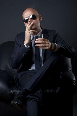 cigar smoking man: empresario fumar y beber sentado en un sof�