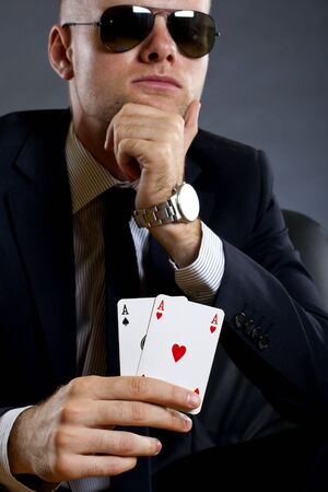 picture of a businessman holding a poker hand - pair of aces photo