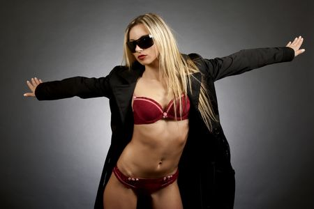 legs open: sexy blond woman wearing raincoat and sunglasses standing with arms wide open