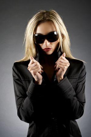 fashion model wearing sunglasses and a black raincoat photo