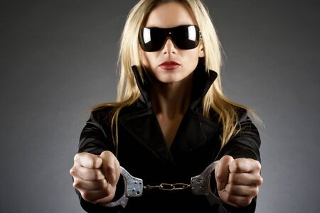 Portrait of beautiful young sexy woman wearing handcuffs, focus on hands photo