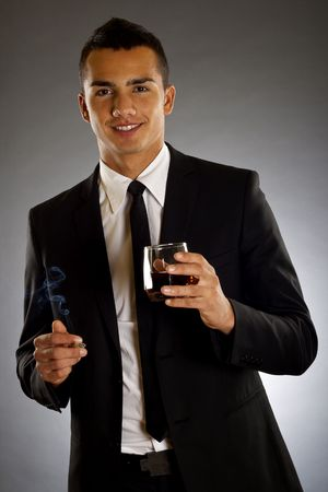 picture of a young businessman drinking and smoking  photo