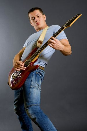 picture of a passionate guitarist playing isolated on dark background photo