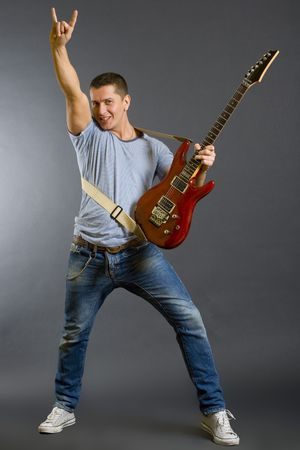 Portrait of a successful rock star holding an electric guitar and making a rock sign on a dark background photo