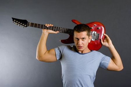 guitarist with electric guitar on his shoulder on dark background photo
