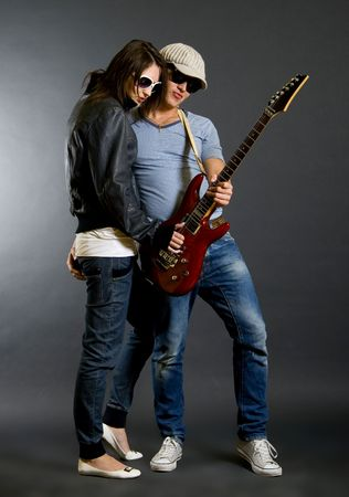 young couple playing together an electric guitar photo