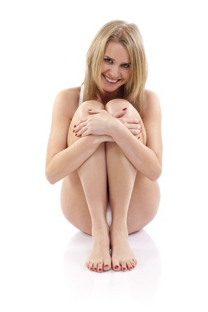 Portrait of young pretty woman sitting hugging legs isolated on white background Stock Photo - 6969934