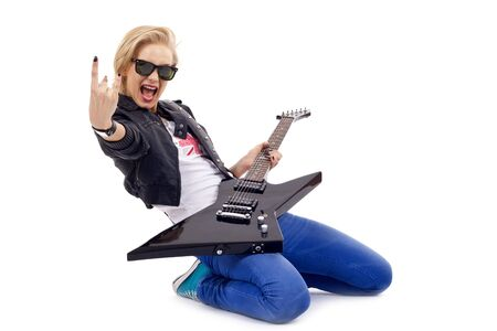 passionate rock girl playing an electric guitar on her knees photo