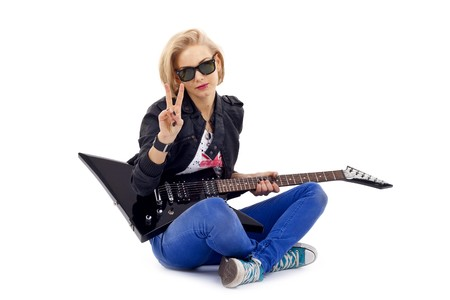 seated woman guitarist making a peace gesture Stock Photo - 6969924