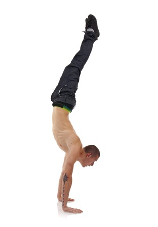 roughneck: young breakdancer in move against grey background - hand stand