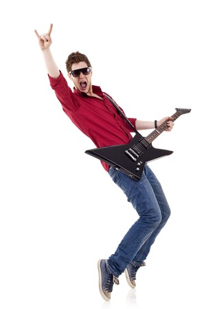 pop singer: Guitar player playing his guitar on his tip toes and make a rock and roll sign