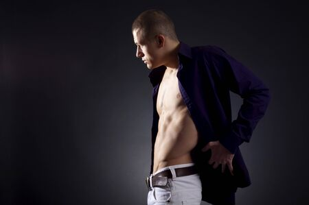 muscle shirt: Beautiful young man posing on dark background , looking towards the light