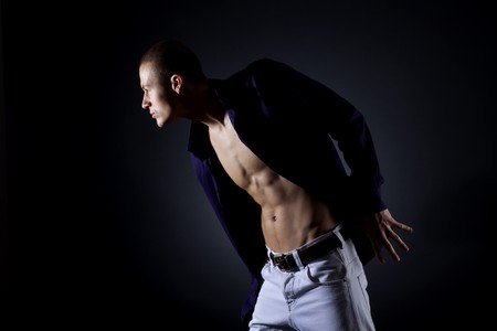 Young fashion man model with athletic body posing on a dark background Stock Photo - 7131982