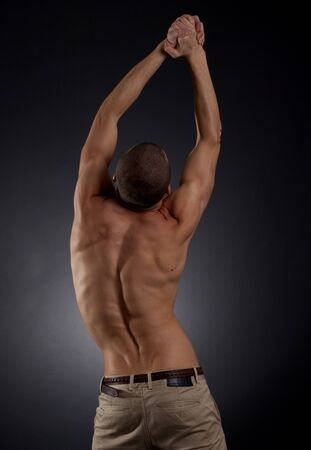 Dramatic image of a beautifully sculpted bodybuilder over dark background photo