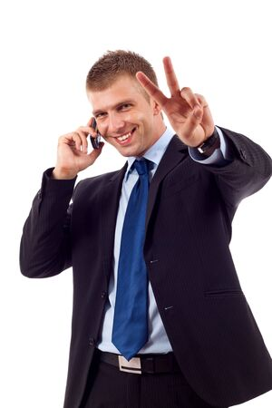 picture of a businessman making victory sign while talking on the phone  photo