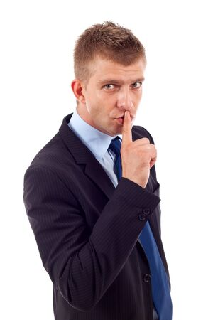 shh: Portrait of businessman showing silence gesture with his forefinger by mouth