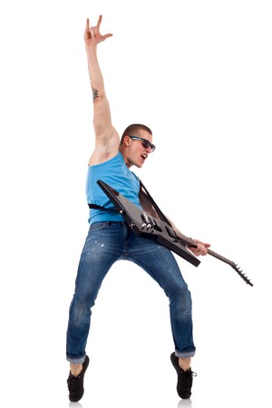 rock   roll: Guitar player playing his guitar on his tip toes and make a rock and roll sign  Stock Photo