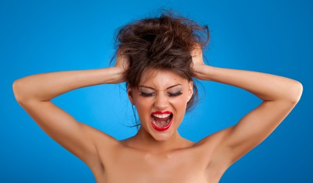 girl screaming and pulling her hair over blue background Stock Photo - 7369362