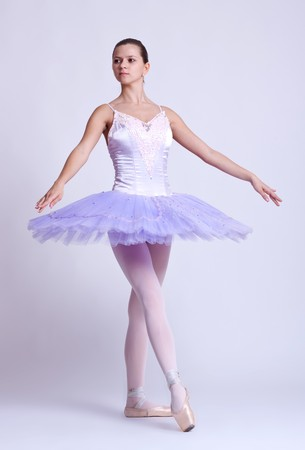 young beautiful ballerina posing in front of gray studio background  photo