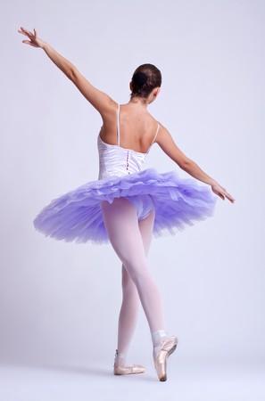 back picture of a ballerina wearing a purple tu tu, studio shot photo