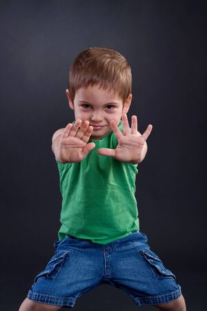 Child looking at camera. Stop signal with his hands. over dark background Stock Photo - 7369389