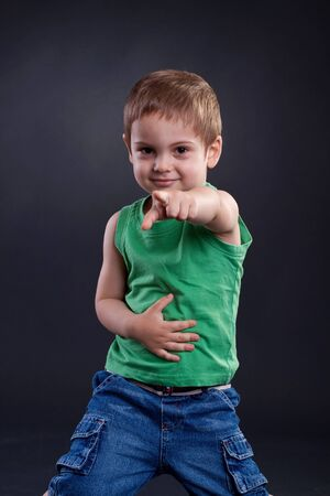 Funny boy pointing the finger a over dark background  Stock Photo - 7369392
