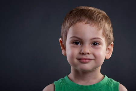 Portrait of an adorable young boy over dark background Stock Photo - 7369378