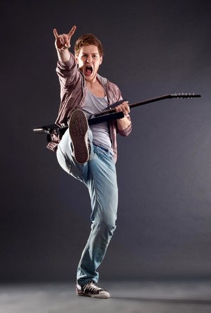 picture of a kicking guitarist playing over dark background  Stock Photo - 7369350