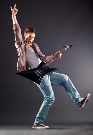 Picture of handsome guitarist making a rock gesture and keeping a leg up photo