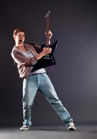 picture of a passionate guitarist playing an electric guitar and sticking the tongue out photo