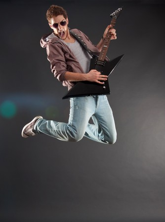 passionate guitarist jumps over dark background - lens flare effect added photo