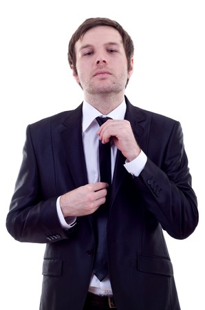 loosen up: picture of a business man adjusting his tie over white